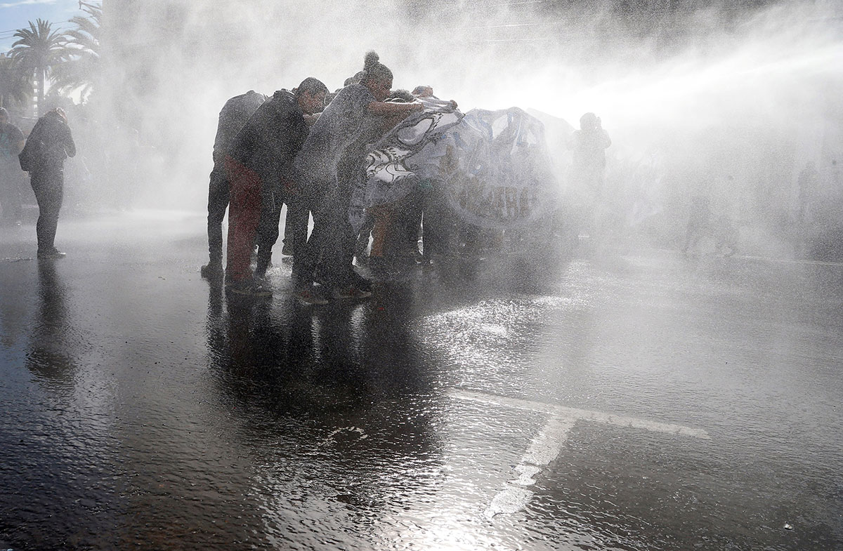 Demonstrators are hit by a jet of water from a riot police vehicle during a protest against government education reforms in Valparaiso, Chile. [Rodrigo Garrido/Reuters]