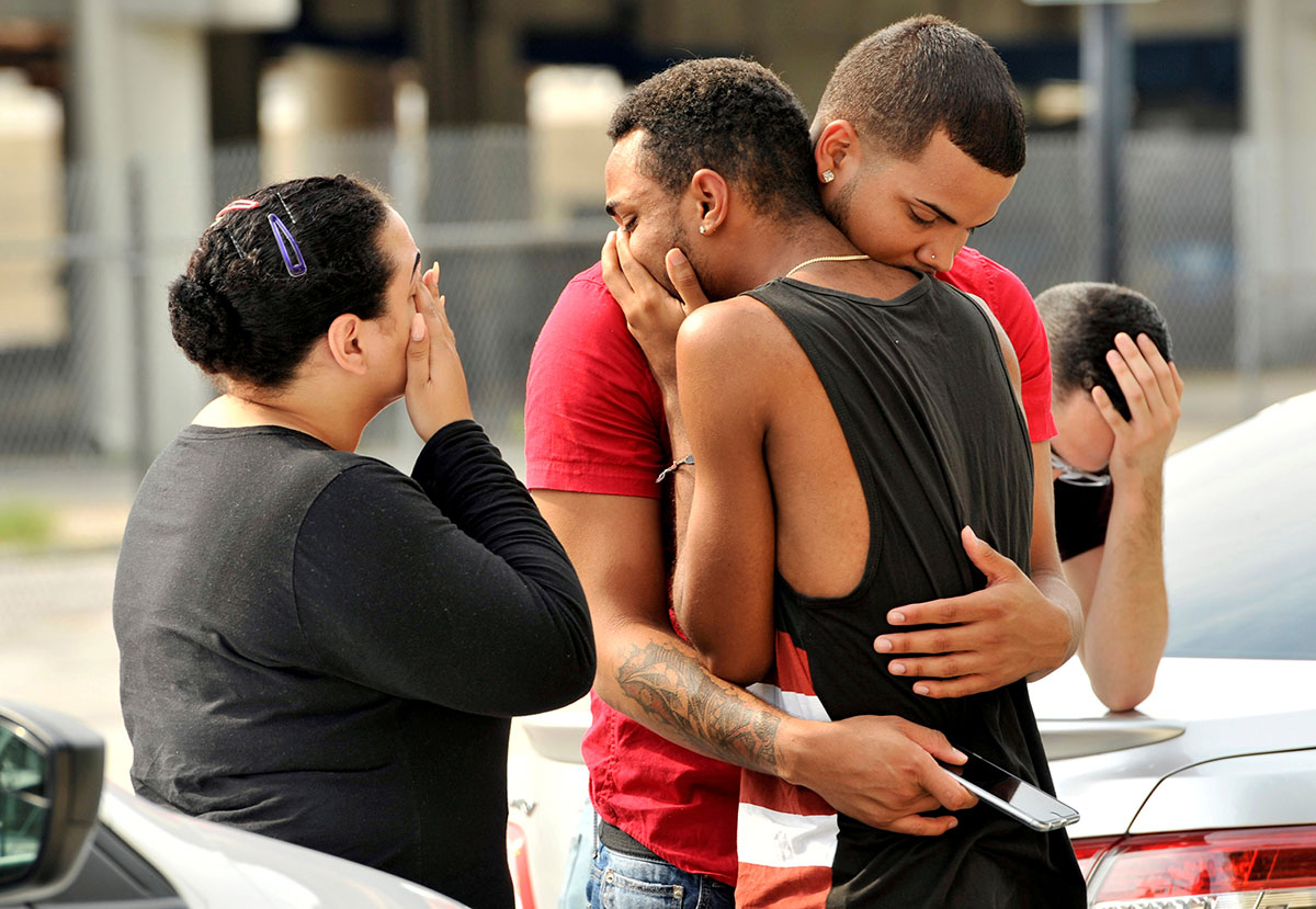 Friends and family members embrace outside the Orlando Police Headquarters during the investigation of a shooting at the Pulse nightclub. [Steve Nesius/Reuters]