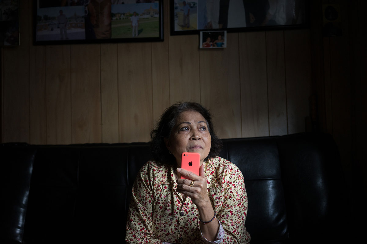 Sokhoeurn Khol, 60, sits alone in her home in southern Philadelphia, speaking by phone to her son Ly Hov Kol, who was deported to Cambodia in 2010 after serving a 12-year prison sentence. Sokhoeurn and her family fled her homeland of Cambodia in 1979, fleeing the brutal regime of the Khmer Rouge who killed an estimated quarter of the population. [Charlotte Pert/Al Jazeera]