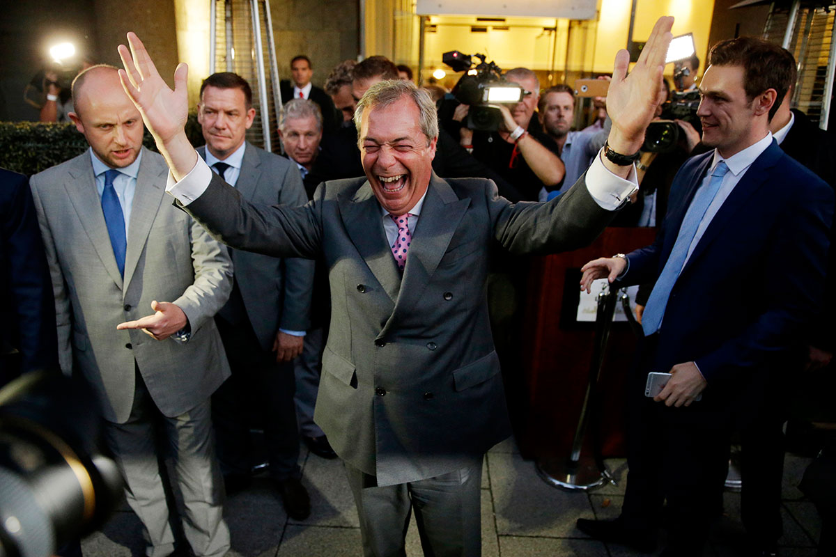 "Nigel Farage, the leader of the UK Independence Party, celebrates and poses for photographs as he emerges from a ""Leave.EU"" organisation party for the British European Union membership referendum in London. On Thursday, Britain voted to leave the EU. [Matt Dunham/AP]"