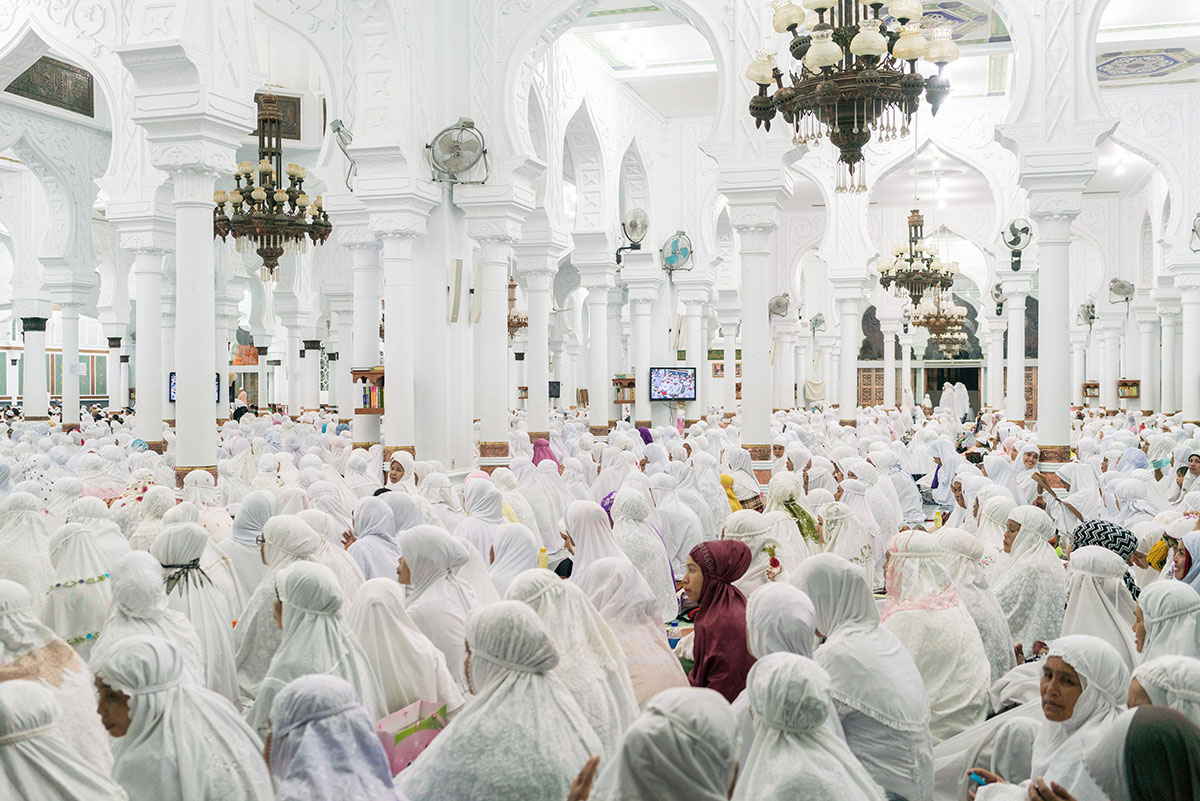 Banda Aceh, Indonesia. Devotees pray inside the Baiturrahman Grand Mosque in central Banda Aceh. The mosque is one of the few buildings that survived the 2004 tsunami, in which more than 170,000 Acehnese lost their lives. [Thomas Cristofoletti/Ruom/Al Jazeera]