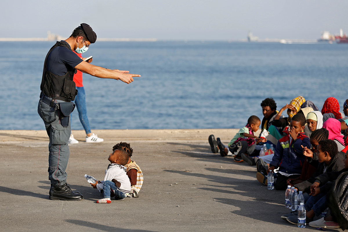 A policeman talks with children as refugees disembark from Offshore Aid Station ship Topaz Responder in the Sicilian harbour of Augusta, Italy. [Antonio Parrinello/Reuters]