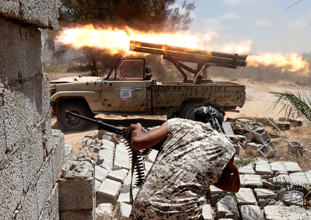 Libyan forces allied with the UN-backed government fire their weapons during a battle with ISIL fighters in Sirte, Libya. [Goran Tomasevic/Reuters]