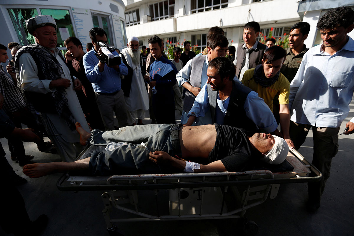 Men transport a wounded person at a Kabul hospital after the suicide attack. [Mohammad Ismail/Reuters]