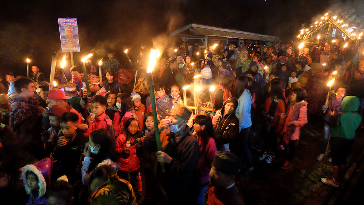 A night before the ceremony, Tenggerese children parade around the village carrying torches. [Syarina Hasibuan/Al Jazeera]