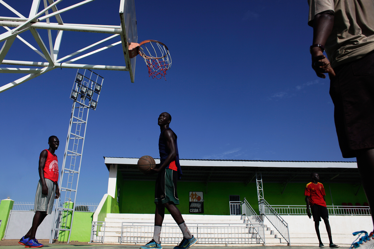 Junior basketball players practise in the early morning on the Nimra Talata basketball stadium, in Juba, before the sun becomes too strong. There are no indoor basketball courts in the city. [Andreea Campeanu/Al Jazeera]