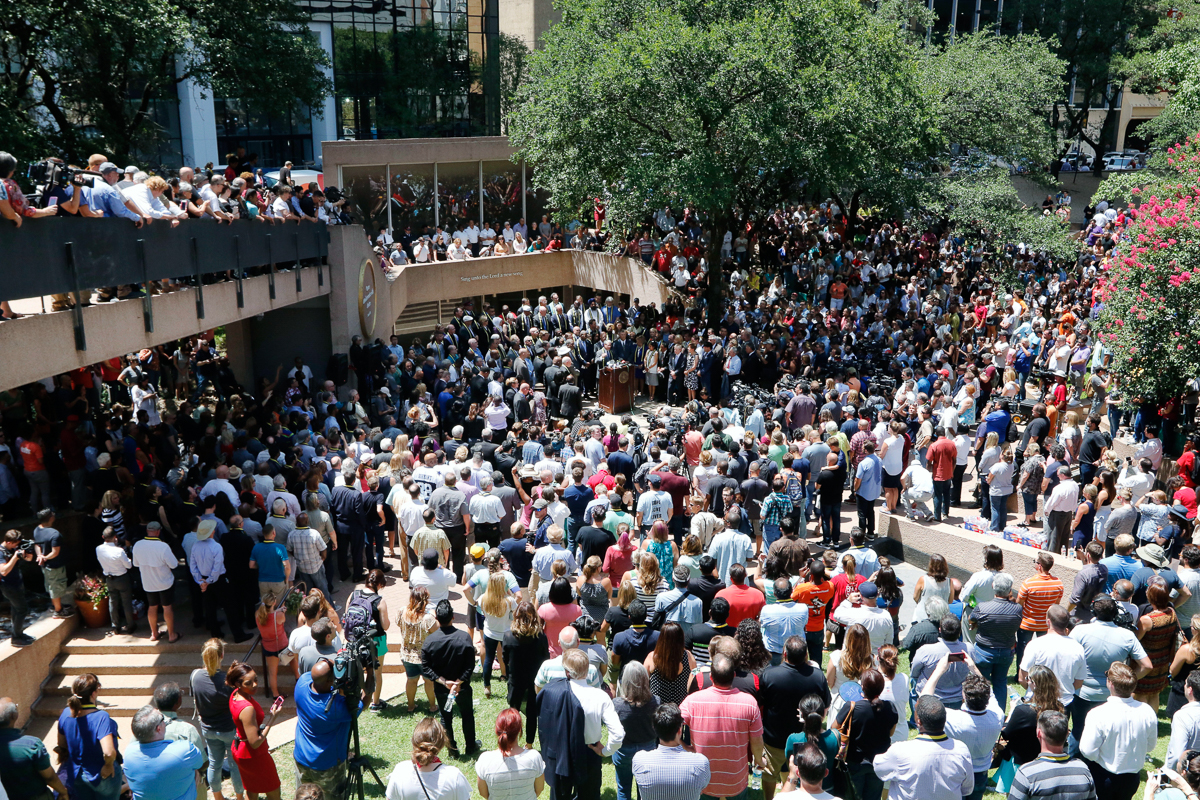People gather to hold a faith vigil during a city-wide prayer service in the city centre. [David Woo/The Dallas Morning News via AP]