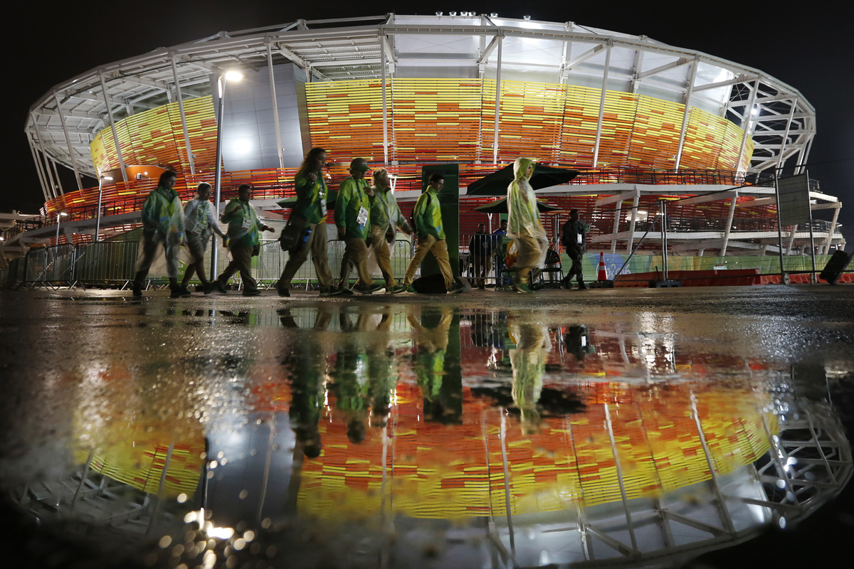 Heavy rain reflected in to the floodlights around the tennis stadium [Michael Reynolds/EPA]