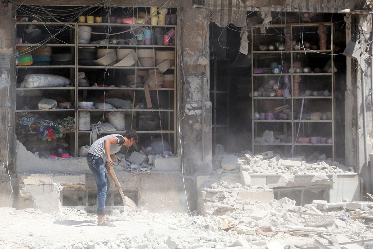 A man removes the rubble in front of a damaged shop after an air strike in the rebel-held al-Saleheen neighbourhood of Aleppo, Syria. [Abdalrhman Ismail/Reuters]