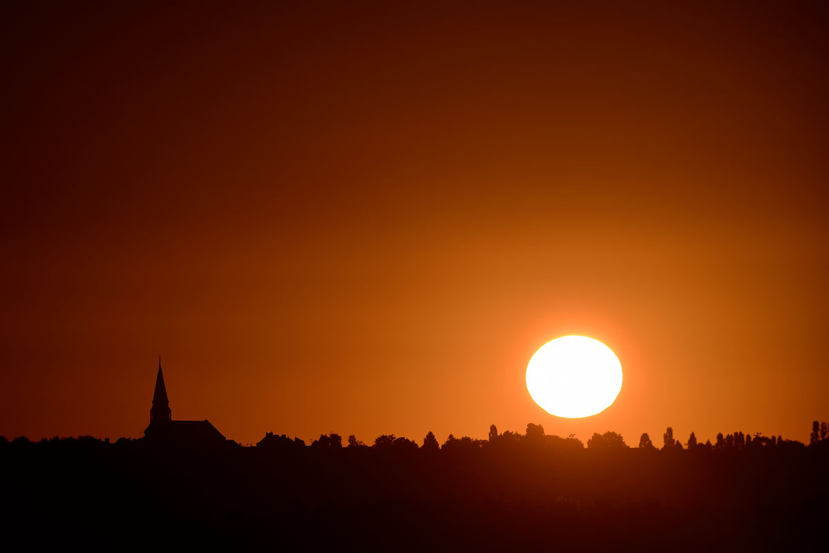 The sun rises over La Roche-Blanche on what is likely to be the hottest day of the year so far in France [Jean-Sebastien Evrard/AFP]