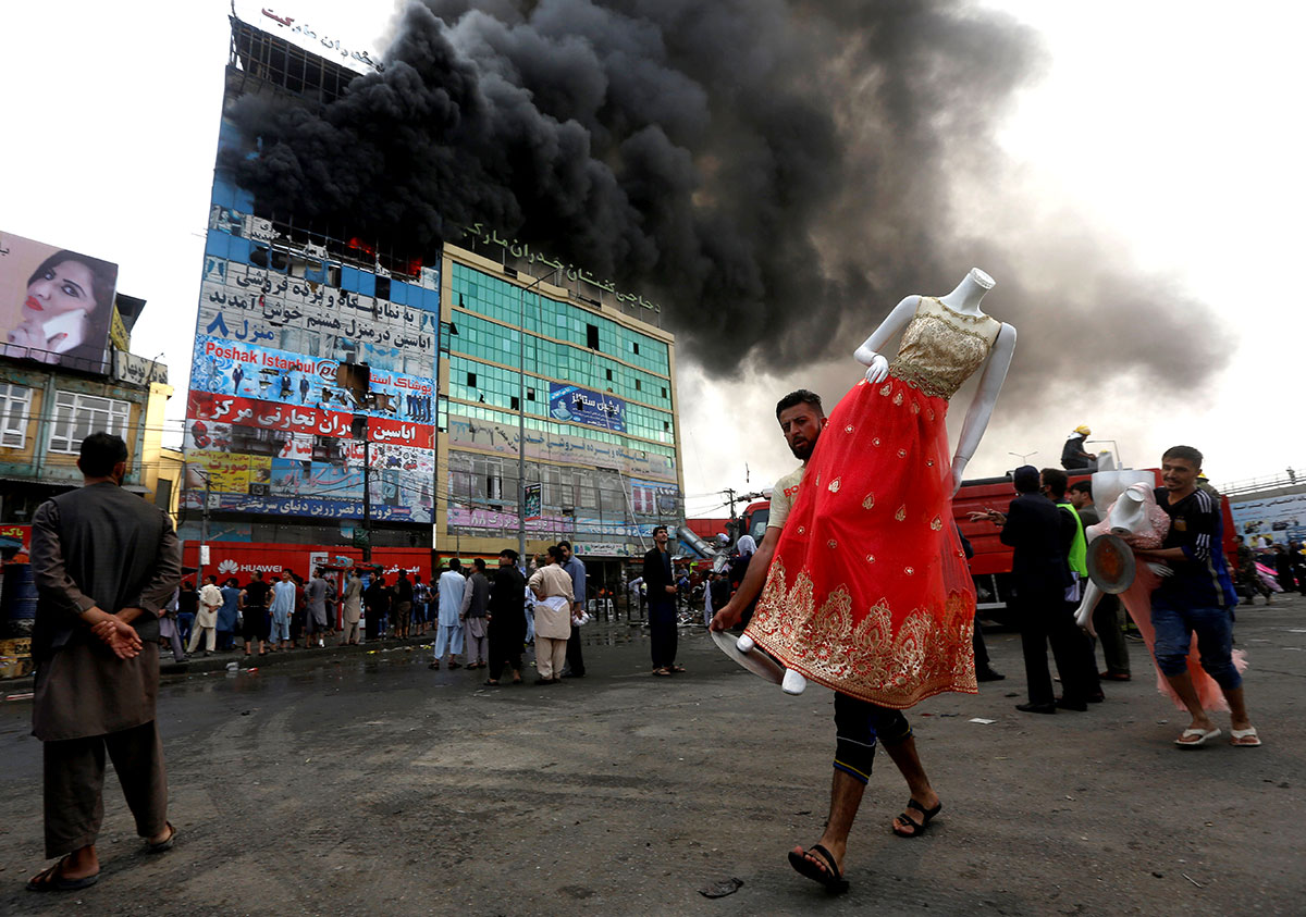 An Afghan shopkeeper carries a mannequin after a fire broke out a shopping mall in Kabul, Afghanistan. [Omar Sobhani/Reuters]