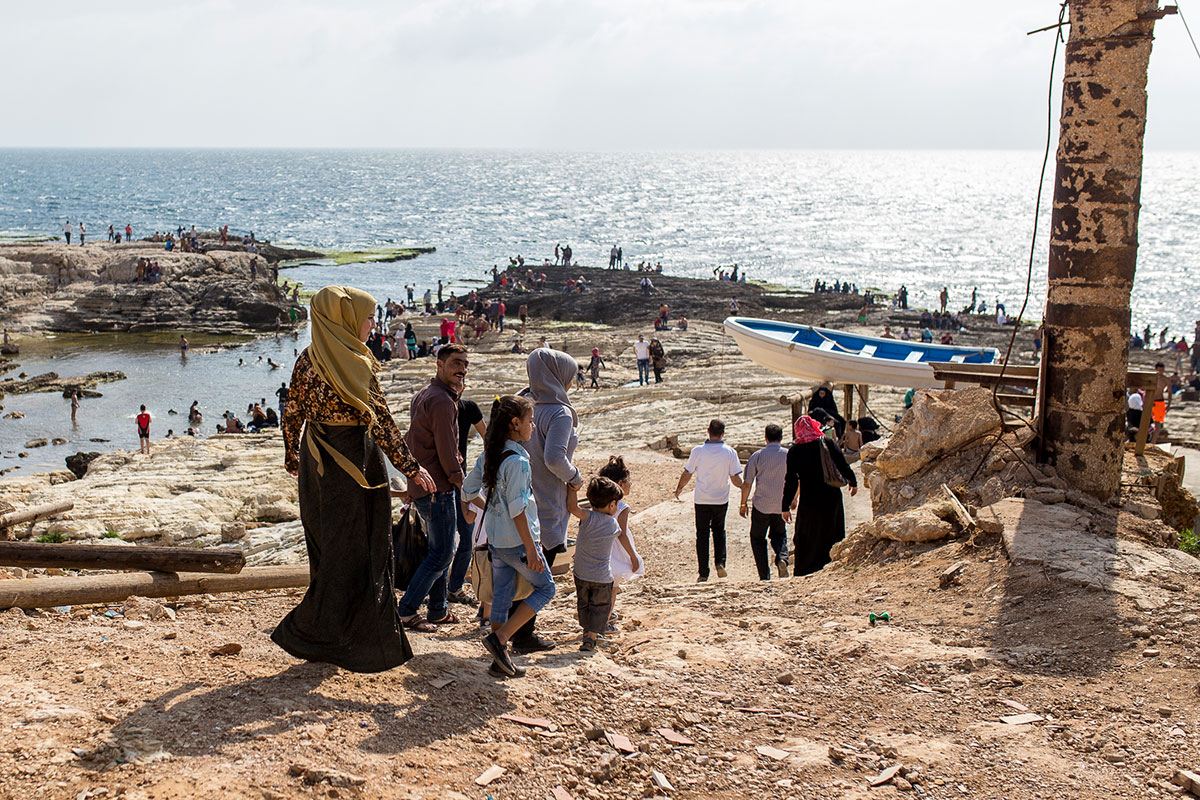 A family descends to Dalieh's tide pools in the late afternoon. As private beaches with entrance fees have increasingly become the norm, those who cannot afford the cost have the choice of Dalieh or the sandy Ramlet al-Baydah beach to the south, which is also threatened by private development. [Kelly Lynn Lunde/Al Jazeera]