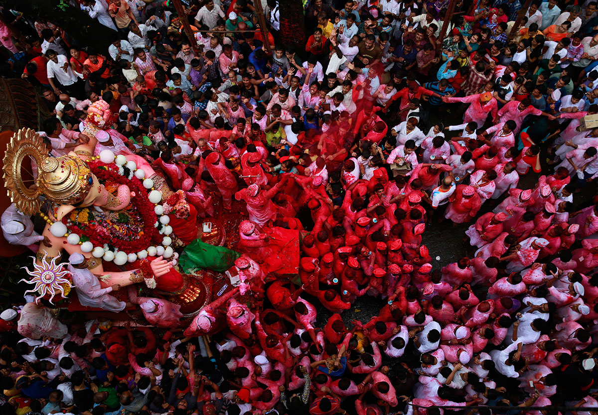 Hindu devotees participate in a procession towards the Arabian Sea where a giant idol of the elephant-headed god Ganesha will be immersed on the final day of the 10-day long Ganesha Chaturthi festival in Mumbai, India.  [Rafiq Maqbool/AP]