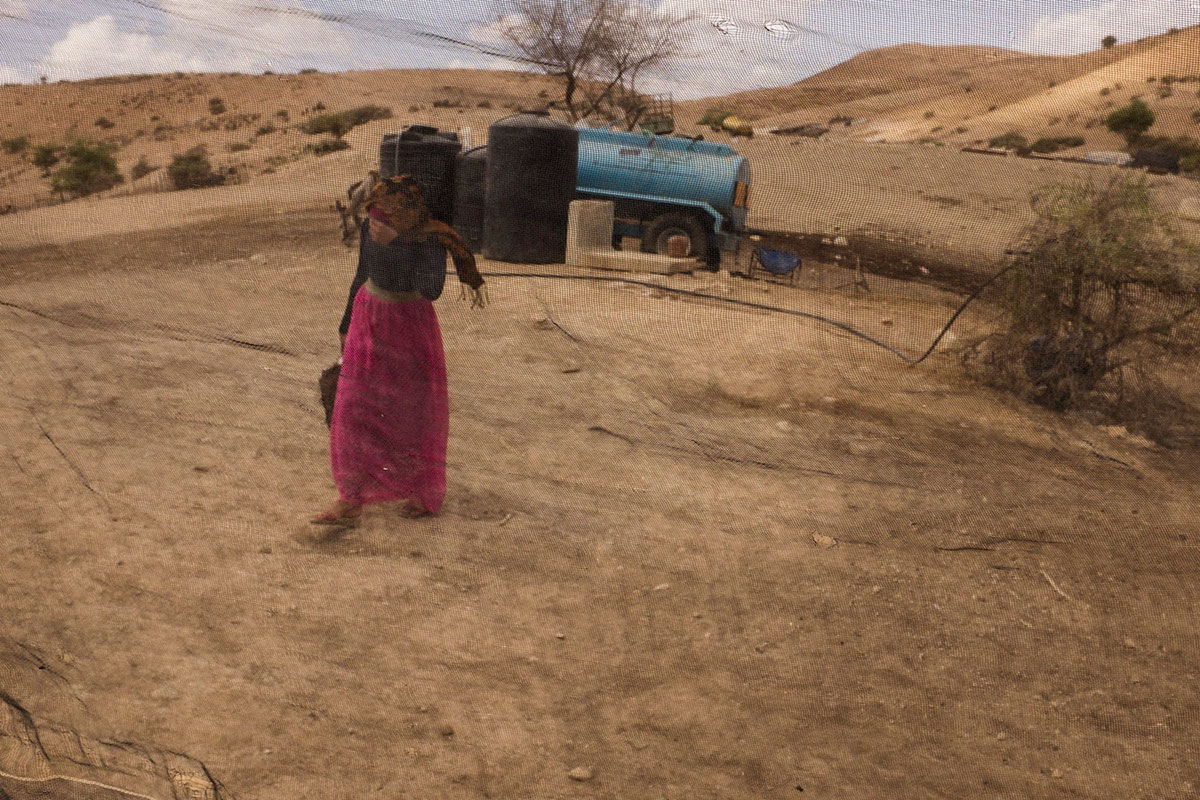 A girl carries water from a village water tank in the Jordan Valley. [Kobi Wolf/Al Jazeera]