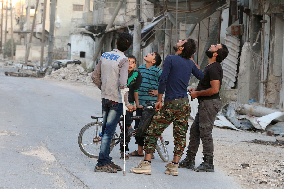 People look at the sky fearing an air strike in the rebel-held al-Myassar neighbourhood of Aleppo. [Abdalrhman Ismail/Reuters]