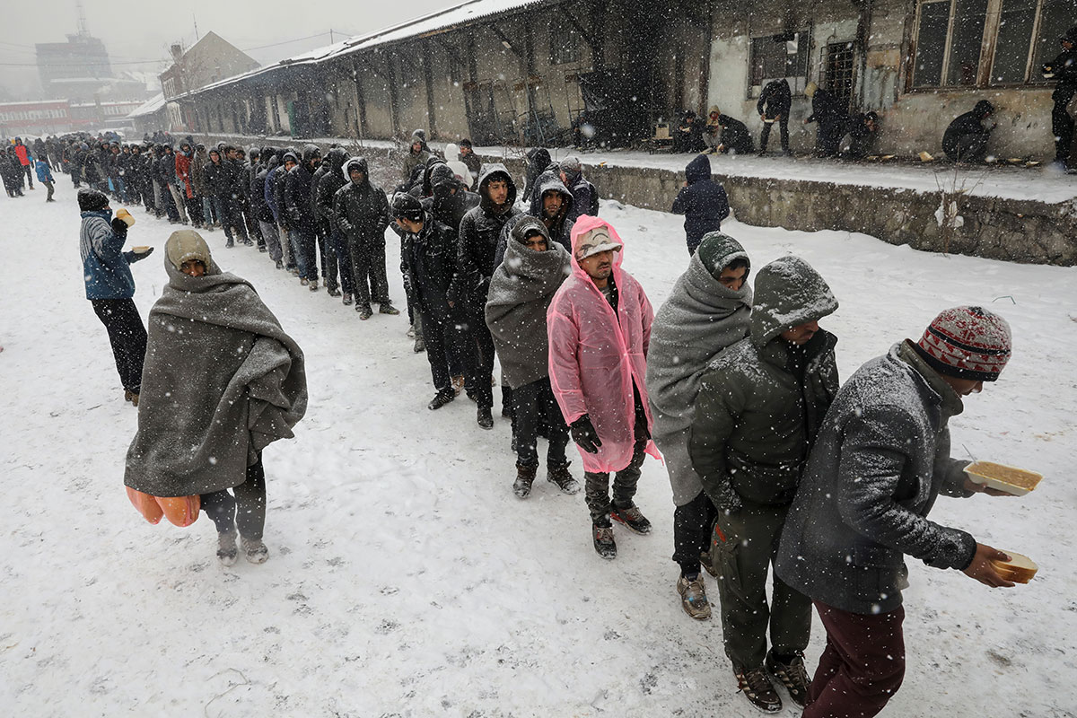 Migrants and refugees stand in line to receive free food outside a warehouse in Belgrade, Serbia. Hundreds are sleeping rough in parks and makeshift shelters in the Serbian capital in freezing temperatures waiting for a chance to move forward towards the EU. [Marko Djurica/Reuters]