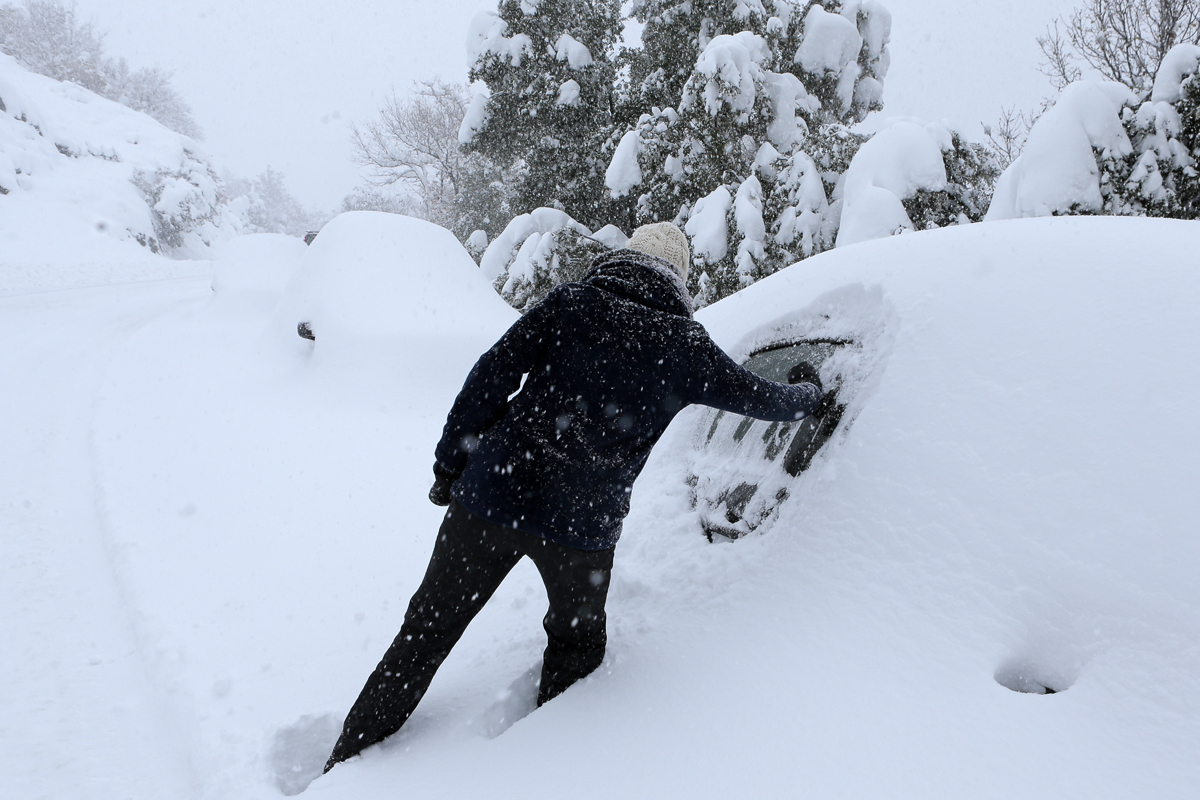 Doing her best to dig out her snowed covered car in Corte, Corsica. [Pascal Porchard-Casabianca/AFP]