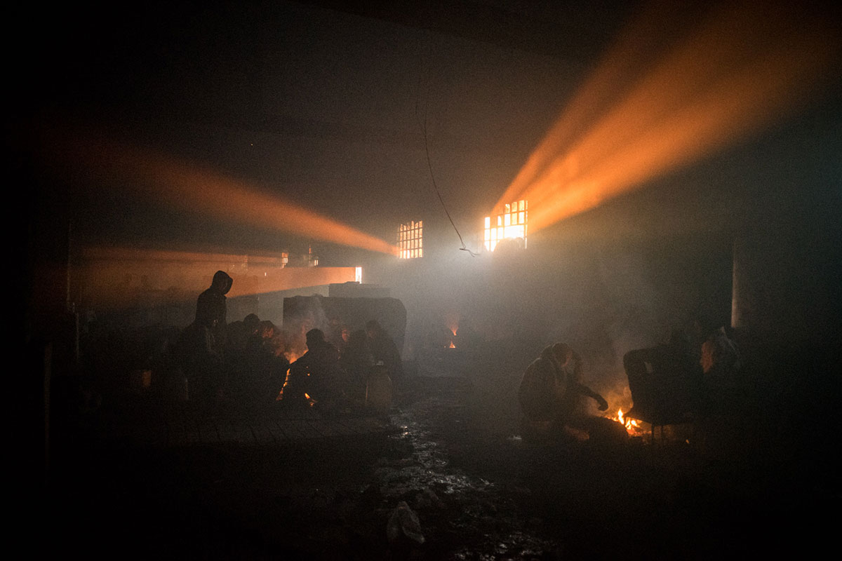 Inside a warehouse where hundreds  of refugees are staying, the air is saturated with smoke from  fires built to keep warm, but breathing is difficult. [Federico Scoppa/CAPTA/Al Jazeera]