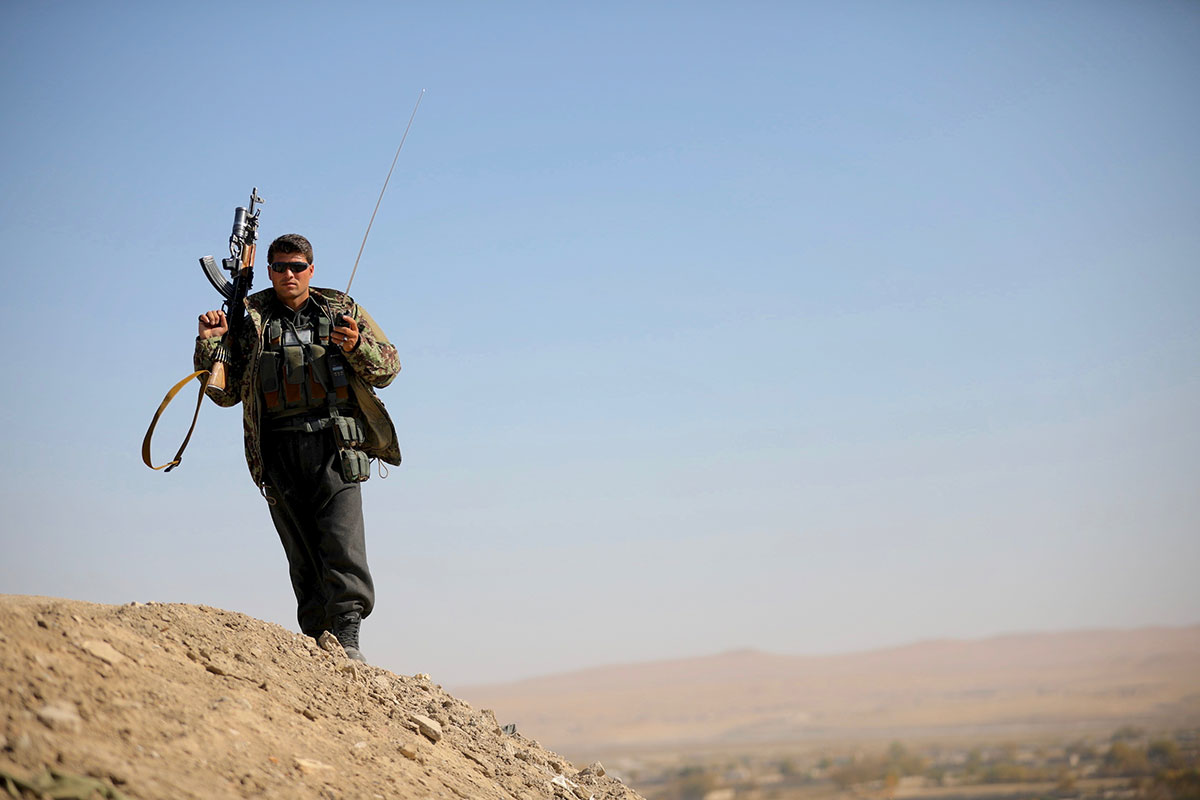 A police officer is on patrol on the outskirts of Lashkar Gah, where Afghan forces are trying to fend off the Taliban. [Steve Chao/Al Jazeera]