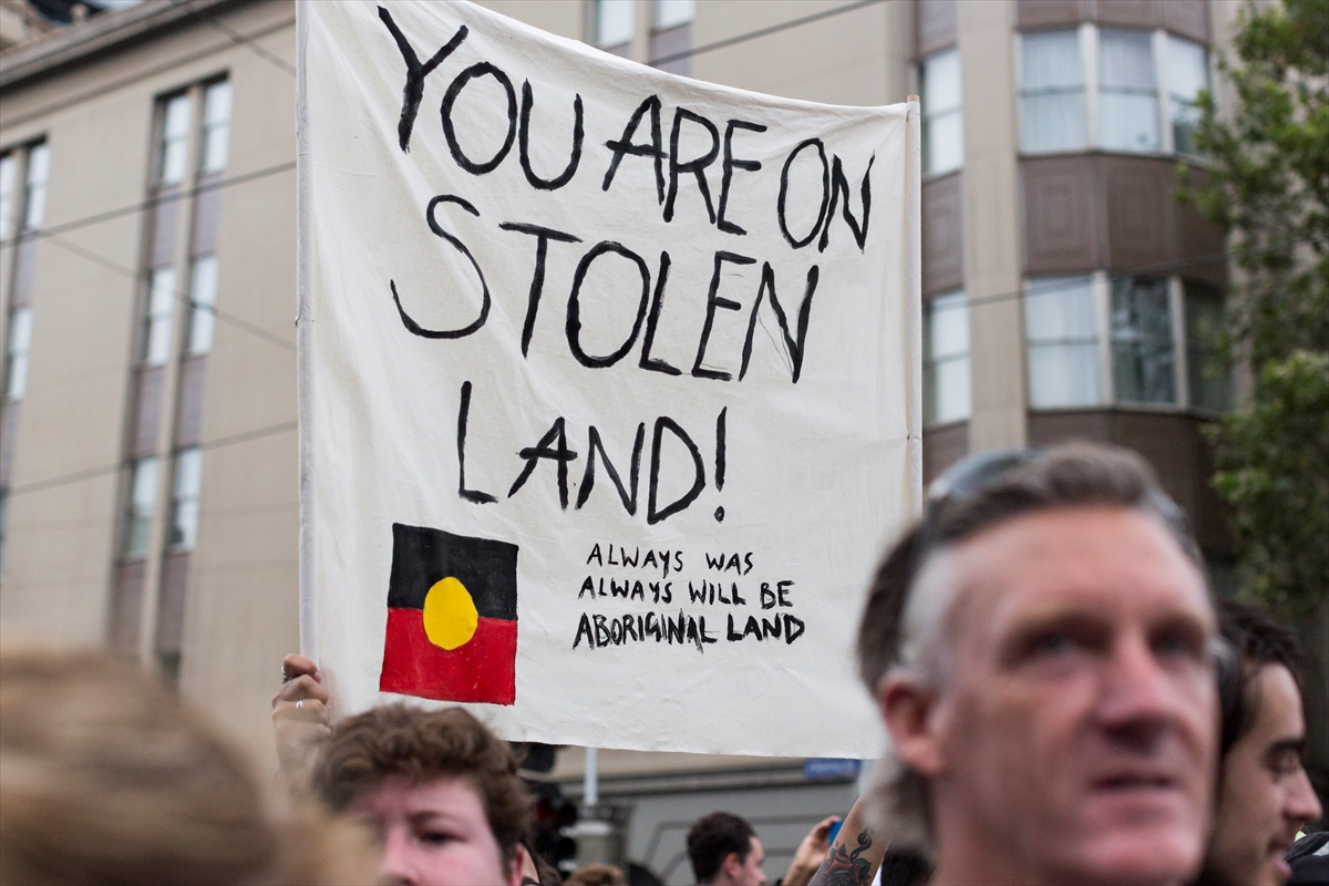 Protesters hold placards during a protest organised by Aboriginal rights activists on Australia Day in Melbourne, Australia. [Asanka Brendon Ratnayake/Anadolu]