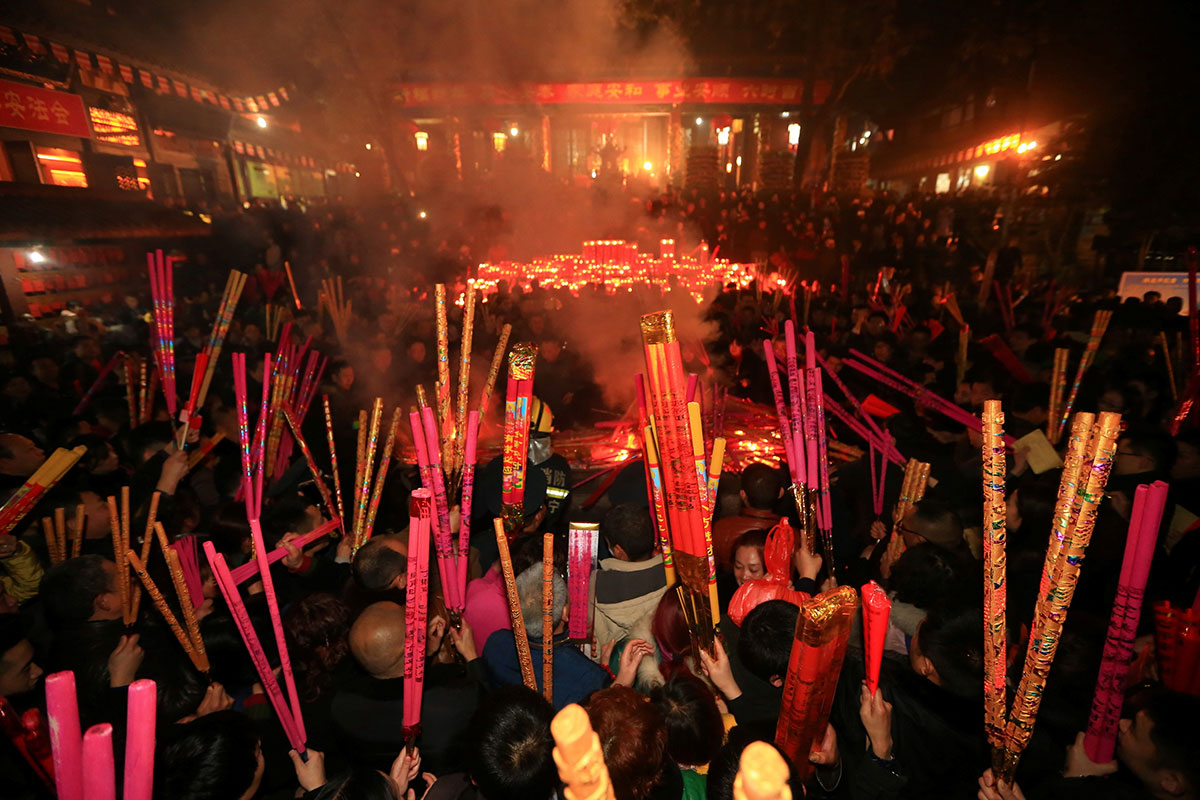 people pray with incense sticks at a temple as they celebrate the lunar new year in - Chinese Lunar New Year