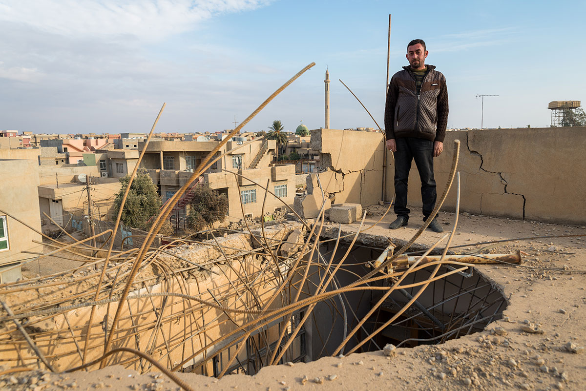 Adnan Mati, 37, stands on the roof of his home, which was hit by an air strike during the battle to retake Qaraqosh from ISIL. [Claire Thomas/Al Jazeera]
