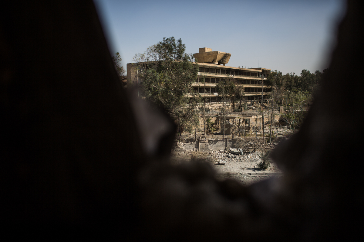 The national hospital where there is a large number of civilians seen through a hole in an SDF forward position, in the west front line of Raqqa. [Mauricio Morales/Al Jazeera]