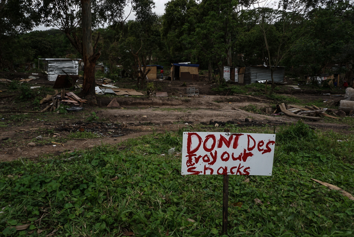 Homes have been destroyed so many times, residents have put up a sign asking for mercy. [Azad Essa/Al Jazeera]