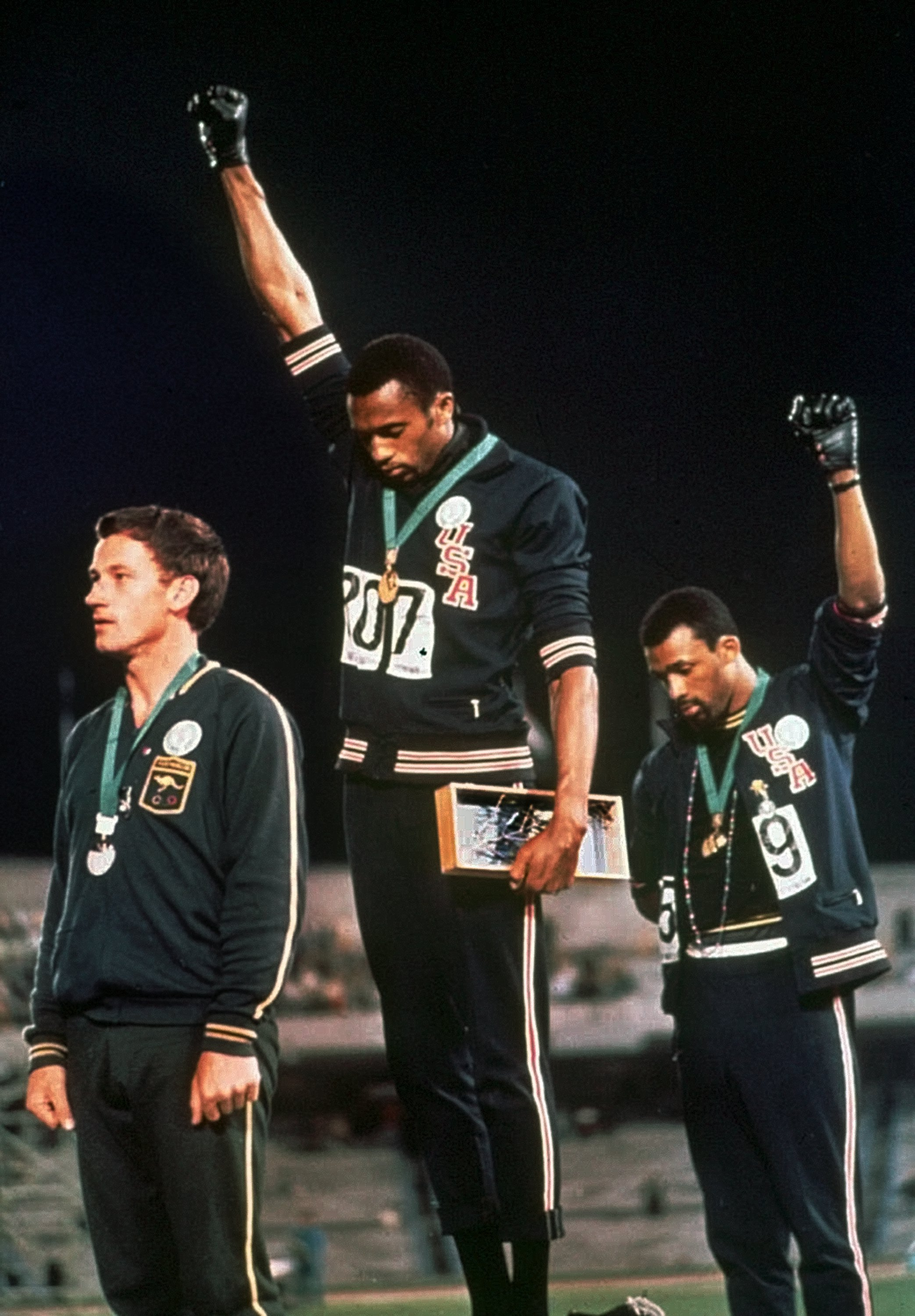 Extending gloved hands skyward in racial protest us athletes tommie smith centre and john carlos right stare downward during the 1968 olympic medal