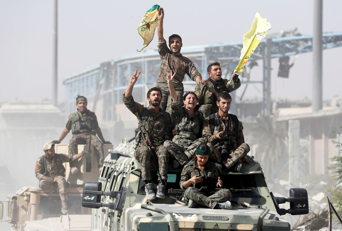 Syrian Democratic Forces (SDF) fighters ride atop military vehicles as they celebrate victory in Raqqa, Syria. [Erik De Castro/Reuters]