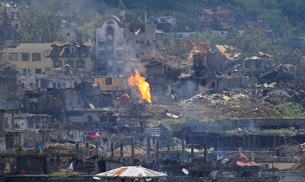 Flames rise from damaged buildings after government troops cleared out pro-ISIL groups inside a war-torn area of Marawi City, in the southern Philippines. [Romeo Ranoco/Reuters]