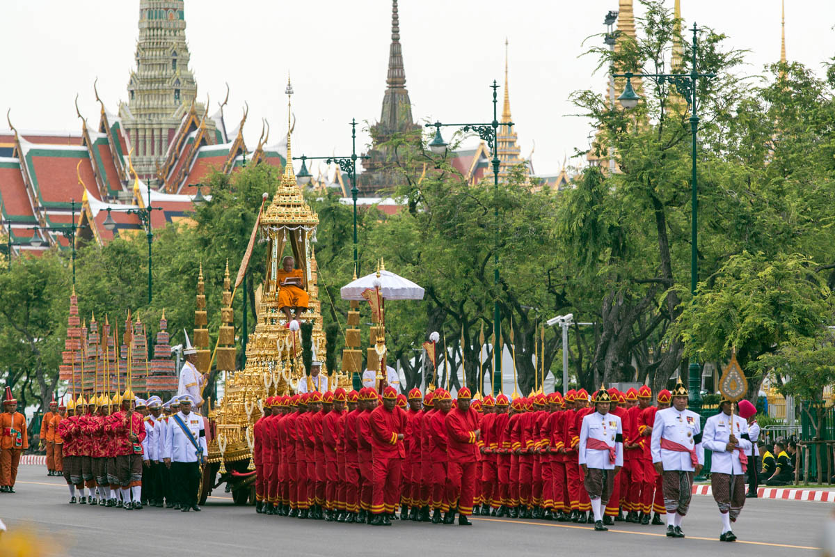 A high-ranking Buddhist monk recites prayers in the small royal chariot as the royal urn of late King Bhumibol Adulyadej heads from the Grand Palace to the Royal Crematory. The chariot is pulled by 42 men in traditional attire. [Alexandra Radu/Al Jazeera]