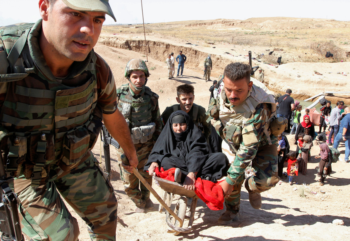 Kurdish Peshmerga forces help those who fled from their homes in Hawija. Iraqi forces captured the town and surrounding area from ISIL this week. It was one of the armed group's last strongholds in Iraq. [Ako Rasheed/Reuters]