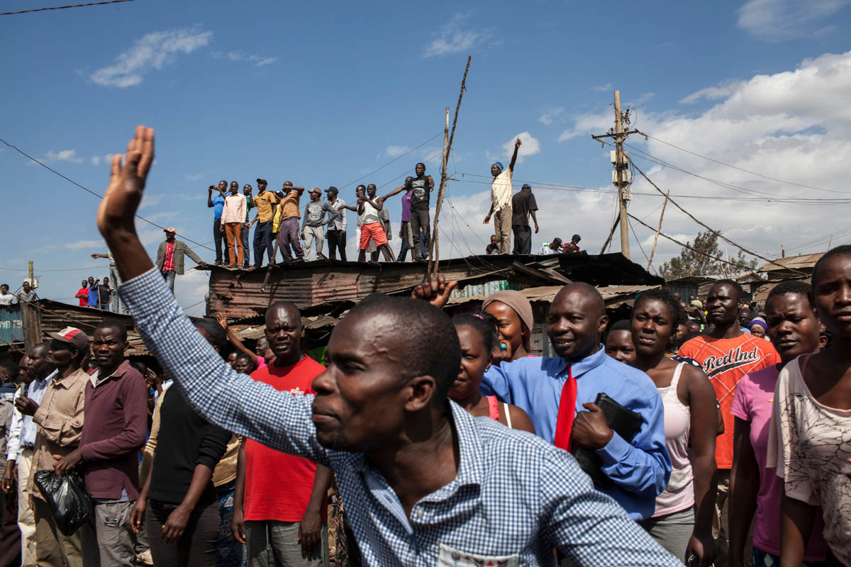 Supporters of Kenya's opposition leader Raila Odinga react as he takes the stage to speak in the Kibera slum of Nairobi. Odinga lost the August 8 election to incumbent Uhuru Kenyatta, however, the election results were later nullified by the country's Supreme Court. [Will Baxter/Al Jazeera]