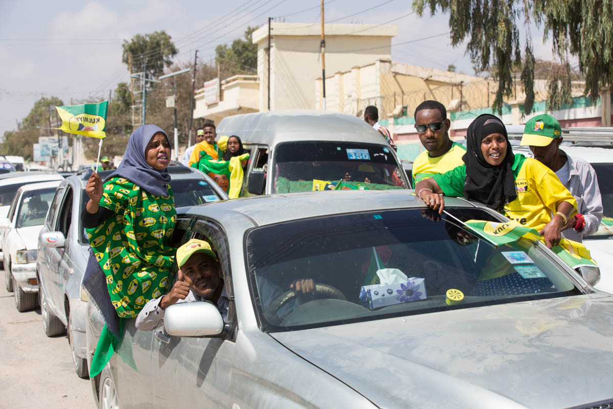 Supporters of Kulmiye (Peace, Unity and Development Party), the current ruling party, drive through the streets of Hargeisa displaying party colours and blaring party-promoting music on their way to a rally. Each day only one designated party can campaign, a rule created to avoid potential conflict and security issues. [Kate Stanworth/Saferworld/Al Jazeera]