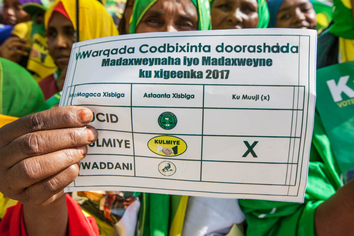 A woman holds up a campaign leaflet in the form of a polling card at a Kulmiye party rally in Hargeisa. Polling cards will include the party symbols to cater for voters who are illiterate. [Kate Stanworth/Saferworld/Al Jazeera]