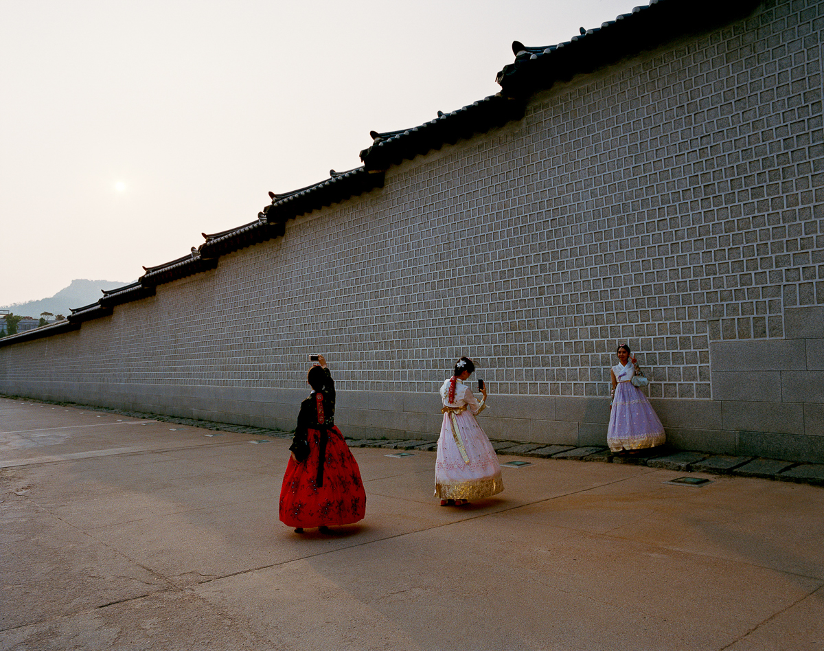 Young women are posing for pictures in front of the Gyeongbokgung-Palace (built in 1395) wearing a Hanbok, Korea's traditional attire, which dates back to the Joseon era (from 1392-1910). In 1427, the Joseon dynasty issued a royal decree banning the performance of Islamic rituals and Muslim traditional attire, as part of an isolationist policy meant to limit contact with foreign countries. [Radu Diaconu/Al Jazeera]