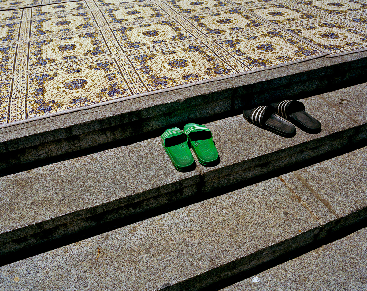 Sandals left at the footstep of the entrance to the main prayer hall. The mosque, which gathers around 800 worshippers every Friday, was built in 1974 and opened its doors in 1976. [Radu Diaconu/Al Jazeera]