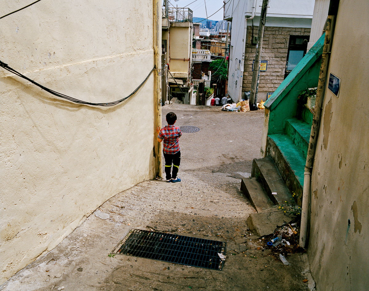 A young boy plays in the streets of the Itaewon neighbourhood. The number of Muslims in South Korea is estimated to be around 100,000 and a large portion of foreign Muslims reside in Itaewon, from countries including Pakistan, Uzbekistan, Senegal, Turkey, and others. [Radu Diaconu/Al Jazeera]