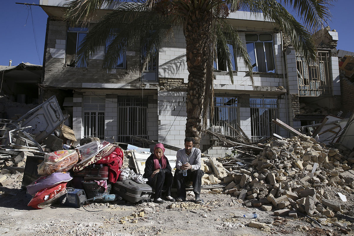 Survivors sit in front of a destroyed house on the earthquake site in Sarpol-e Zahab in western Iran. [Vahid Salemi/AP Photo]