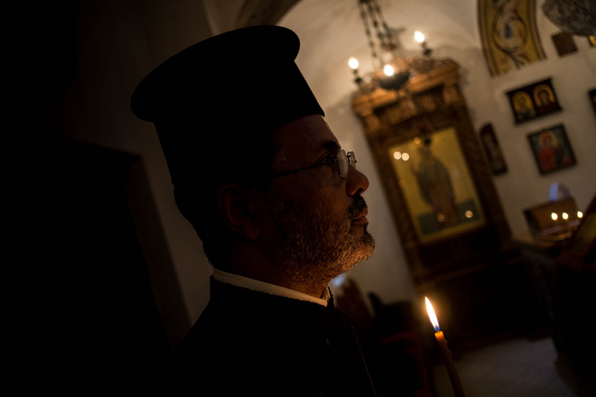 One of the fathers of the Greek Orthodox Church recites his prayers. The community of this church has grown in recent years. [Ura Iturralde/Al Jazeera]
