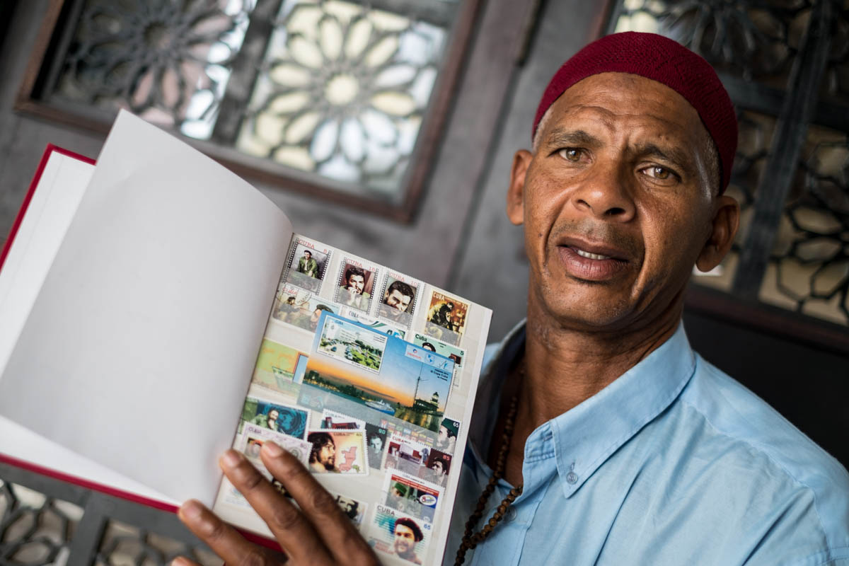 This man, who converted to Islam several years ago, shows his collection of stamps of Che Guevara. [Ura Iturralde/Al Jazeera]