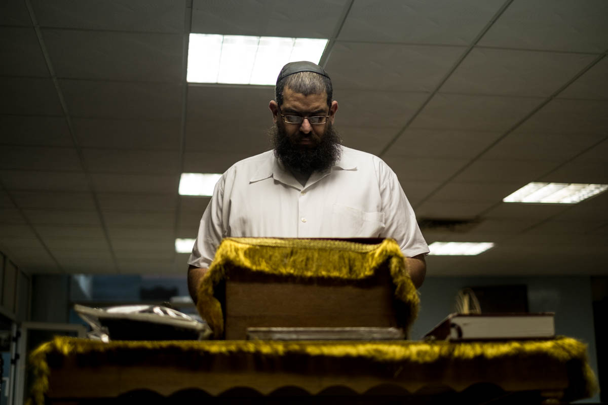 Yacob of Adath Israel reads the Torah. Daily religious services are held here. [Ura Iturralde/Al Jazeera]