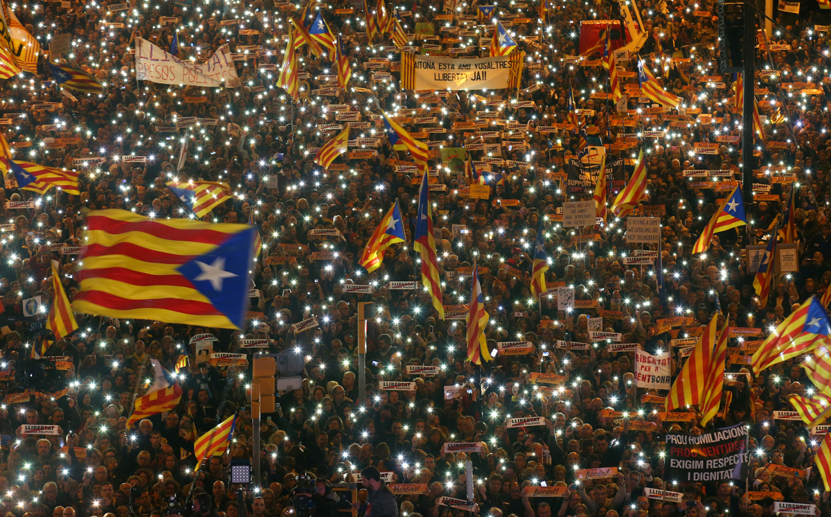Protesters hold their lit-up mobile phones as they wave Estelada flags during a demonstration called by pro-independence associations in Barcelona, Spain, asking for the release of jailed Catalan activists and leaders. [Albert Gea/Reuters]