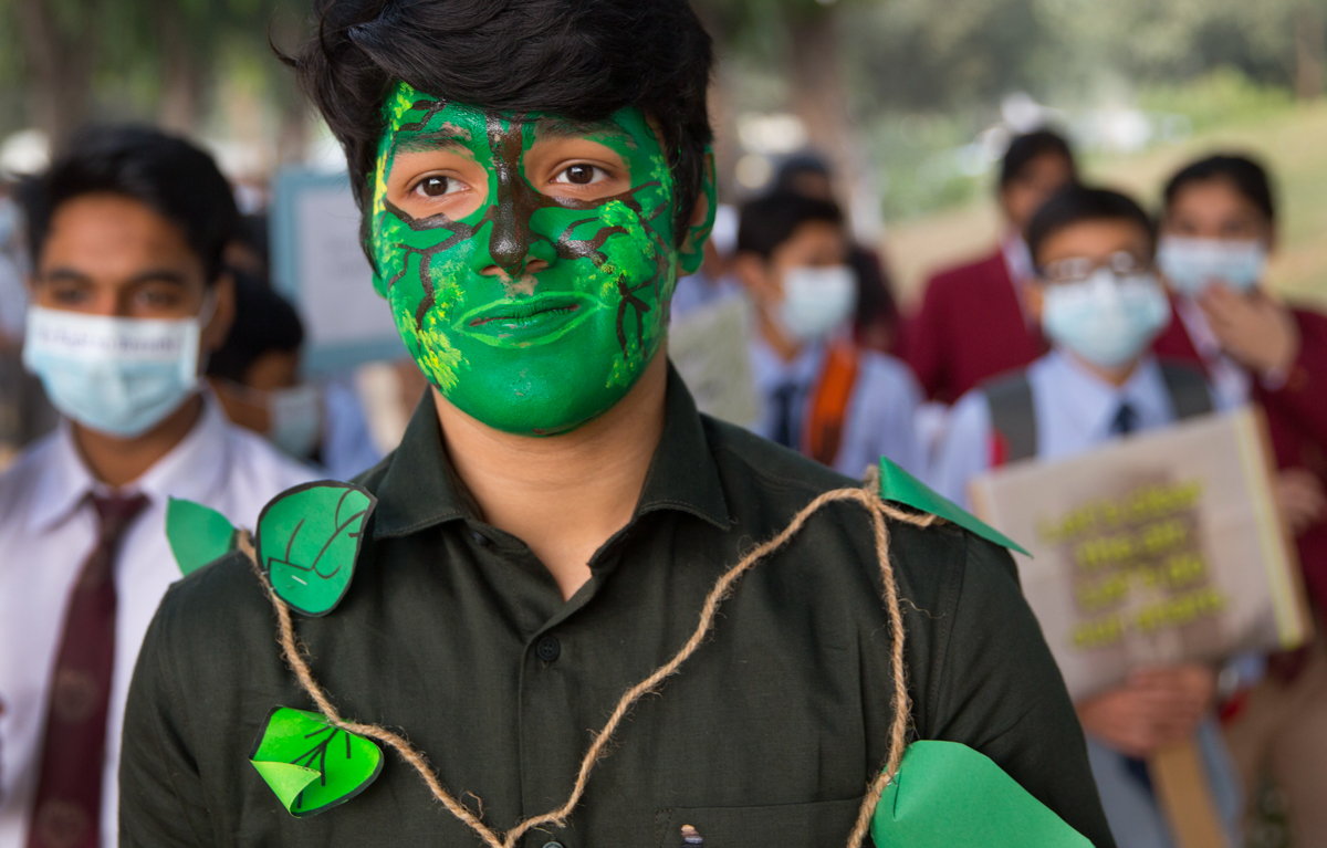 A young man with his faced painted to look like a tree participates in a march with other schoolchildren to express their distress over the alarming levels of pollution in New Delhi, India. [Manish Swarup/AP Photo]