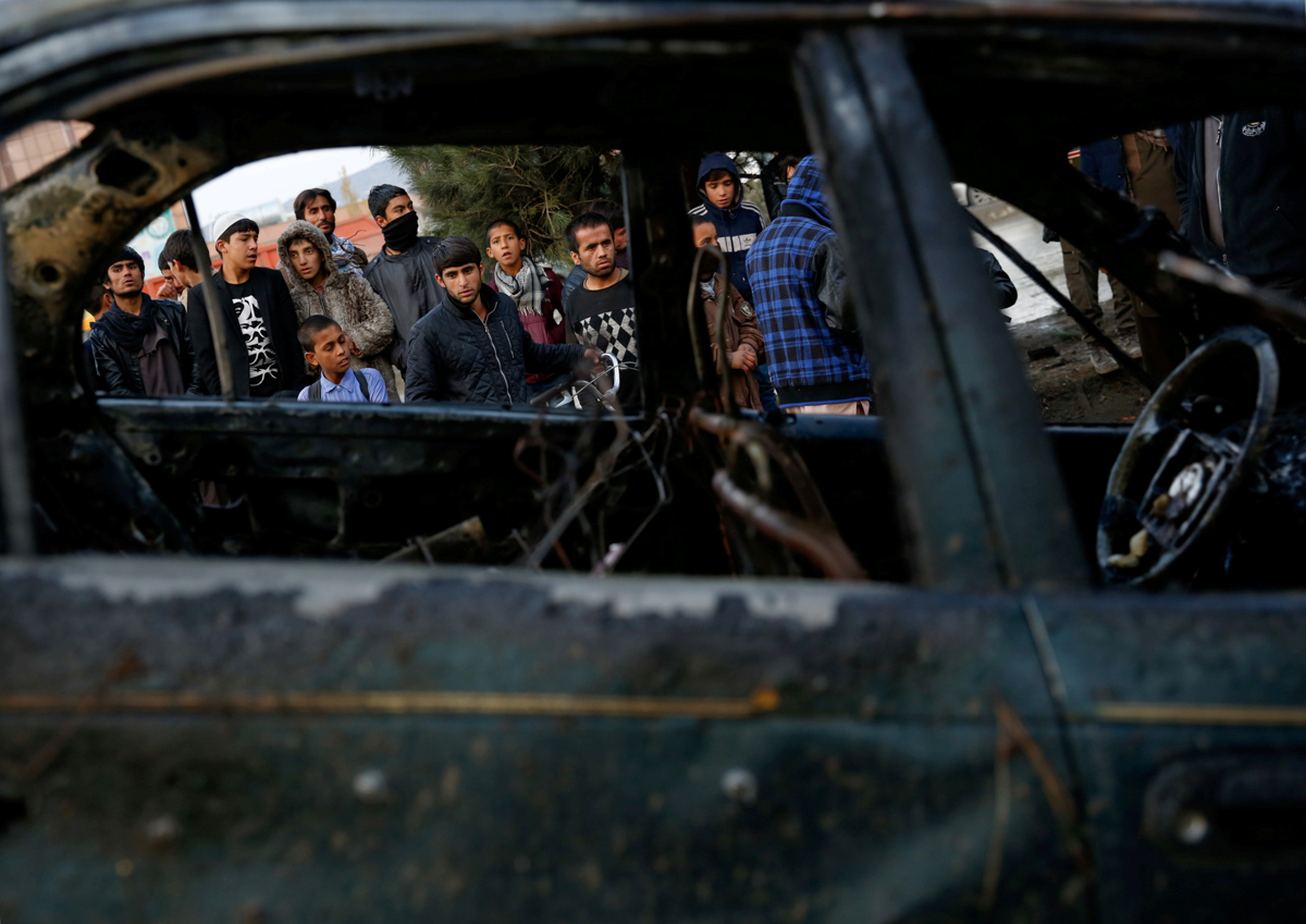 People look at a destroyed vehicle after a suicide bomber detonated in Kabul, Afghanistan. [Mohammad Ismail/Reuters]