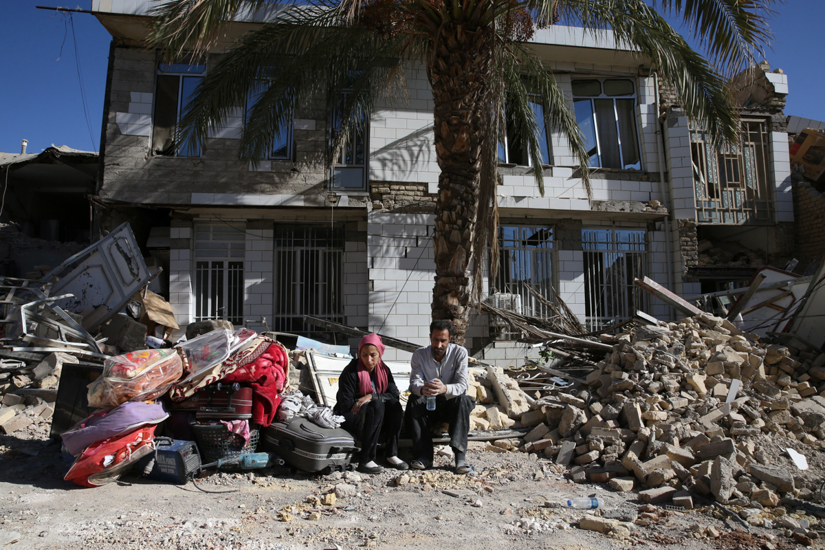 Survivors sit in front of a destroyed house at the site of an earthquake in Sarpol-e-Zahab, in western Iran. [Vahid Salemi/AP Photo]
