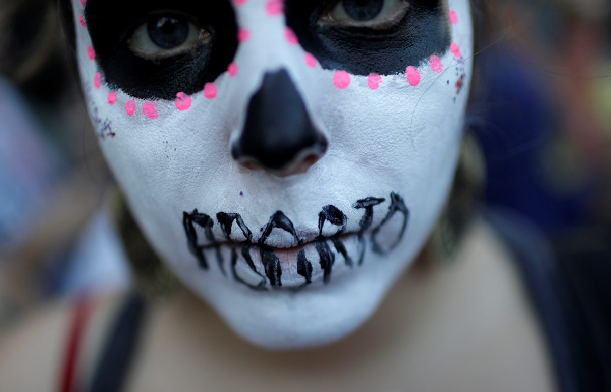 A woman demonstrates against Brazil's congressional move to criminalise all cases of abortion, including cases of rape and where the mother's life is in danger, with a face painting representing a woman dead after an illegal abortion, in Rio de Janeiro, Brazil. [Ricardo Moraes/Reuters]