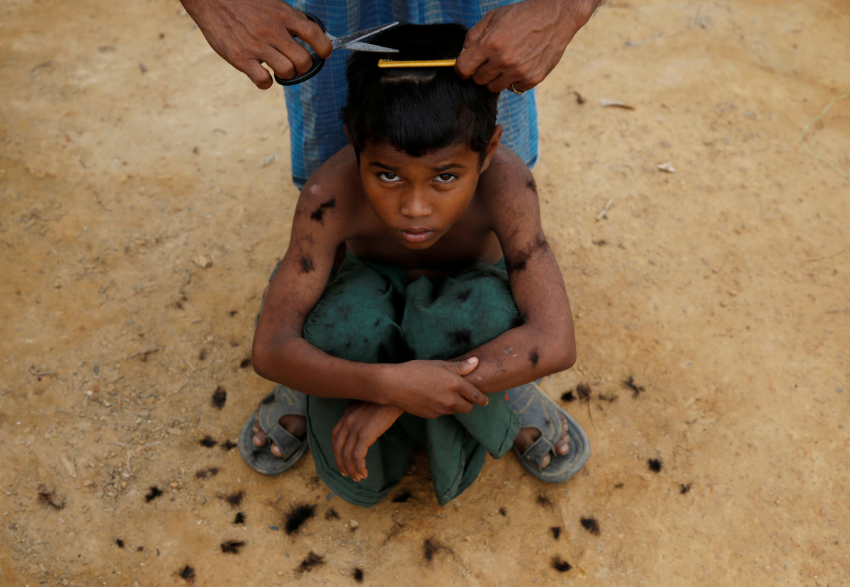 A Rohingya refugee boy gets a haircut at Kutupalong refugee camp near Cox's Bazar, Bangladesh. [Navesh Chitrakar/Reuters]