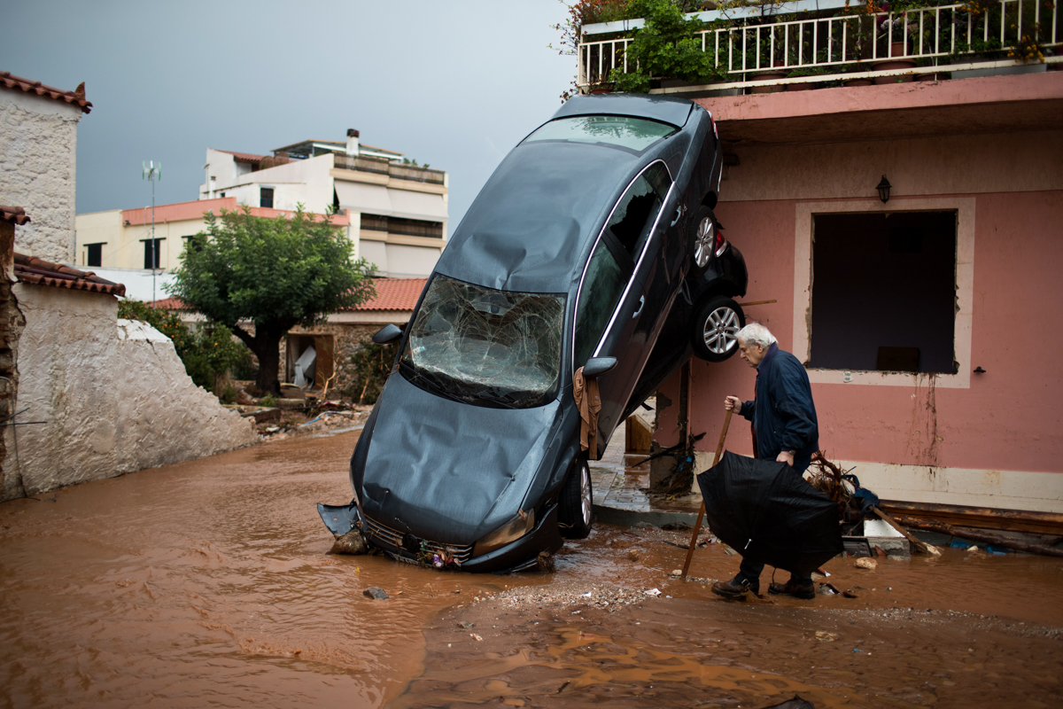 A man walks past a car moved by the force of floodwaters and a damaged house in the town of Mandra, in western Athens. Greek officials said that rescue crews were searching for six people reported missing in the area after major flash flooding that left at least 14 people dead. [Petros Giannakouris/AP Photo]